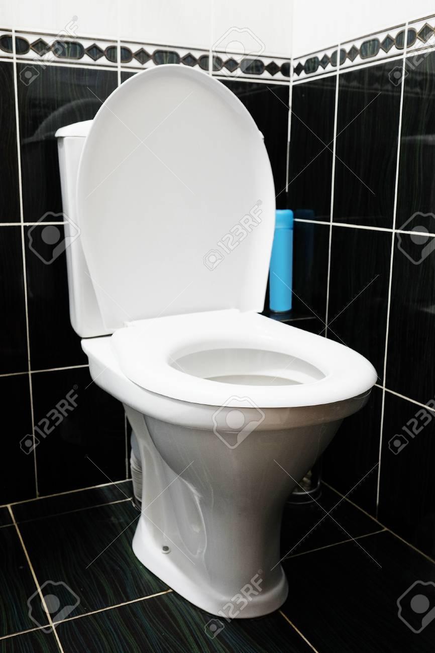 White Ceramic Toilet In Black Tiled Bathroom Stock Photo, Picture ...