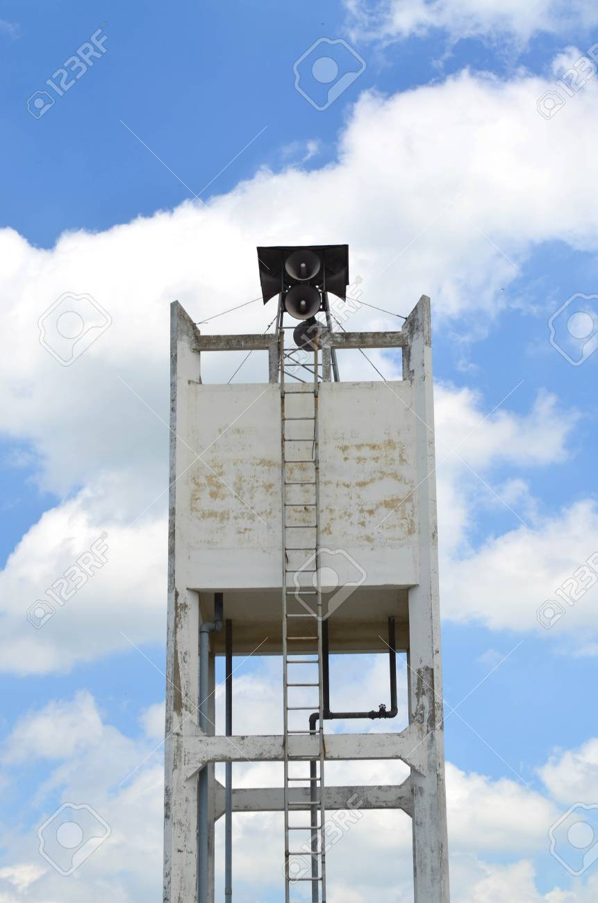 Square concrete water tower tank against hazy blue sky