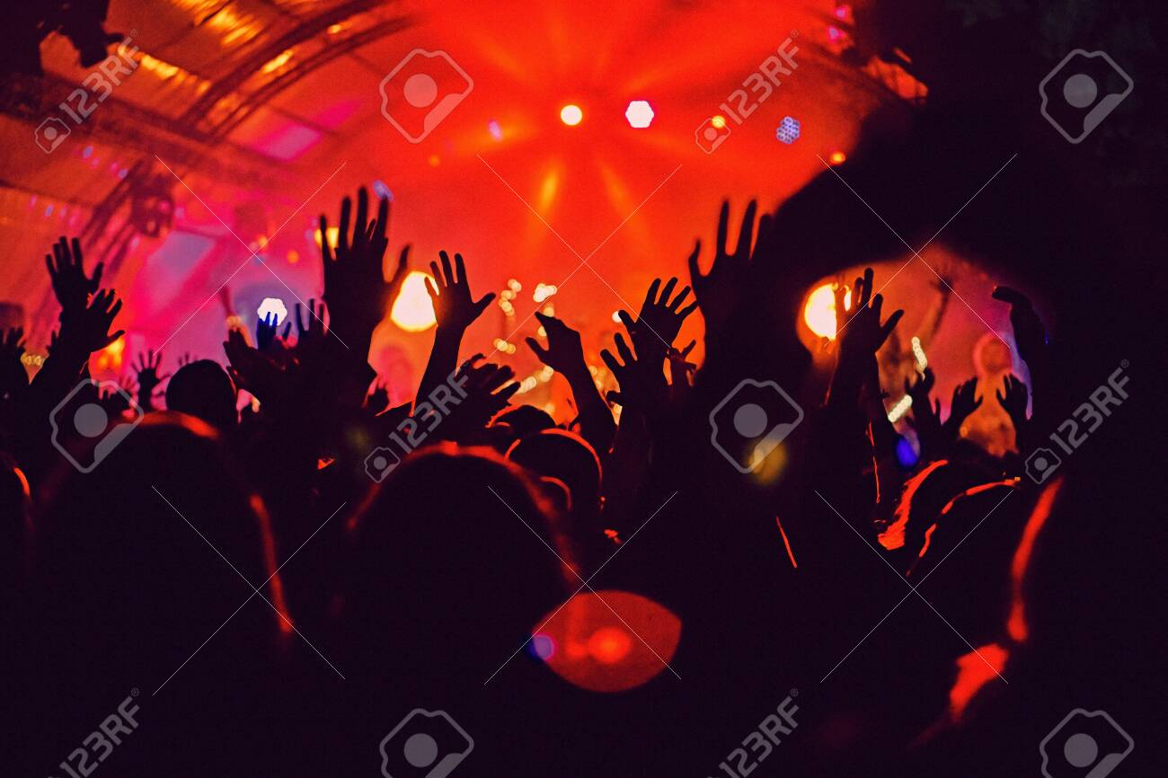 Abstract blur atmosphere: happy people enjoying outdoor music festival concert, raised up hands and clapping of pleasure, active night life concept, play of light and shadow on the huge stage - 158985772