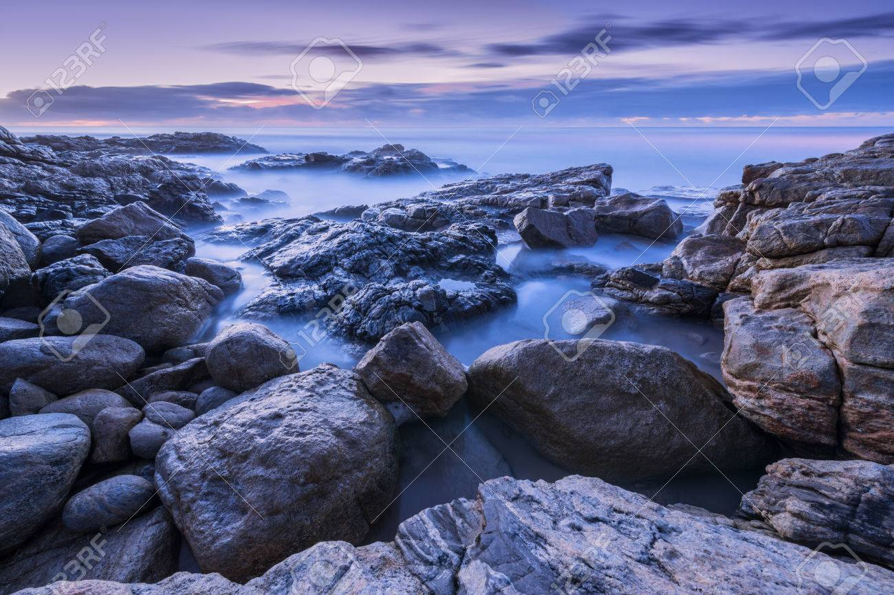 Pre-dawn photograph of misty waves crashing on the rocks by the South Coast in South Africa Standard-Bild - 28649690
