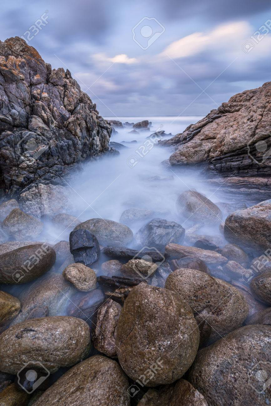 Sunset photograph of misty waves crashing on the rocks by the South Coast in South Africa Standard-Bild - 29688559