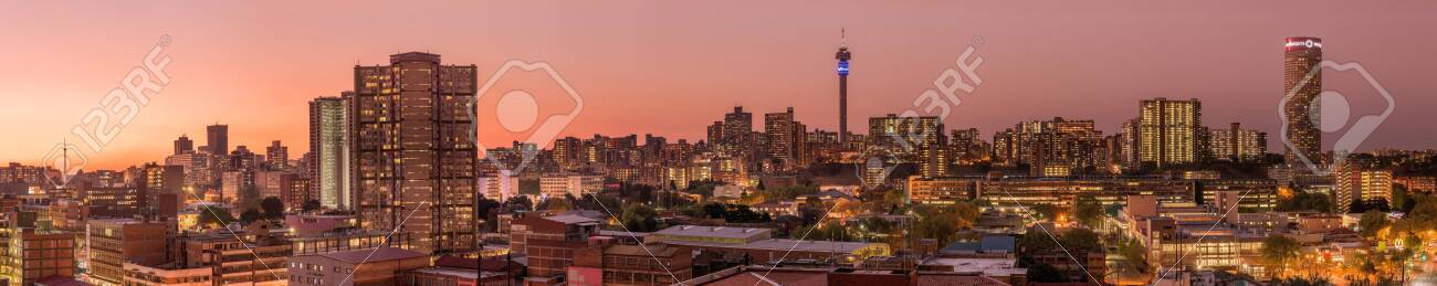 A beautiful and dramatic panoramic photograph of the Johannesburg city skyline, taken on a golden evening after sunset. - 142555825