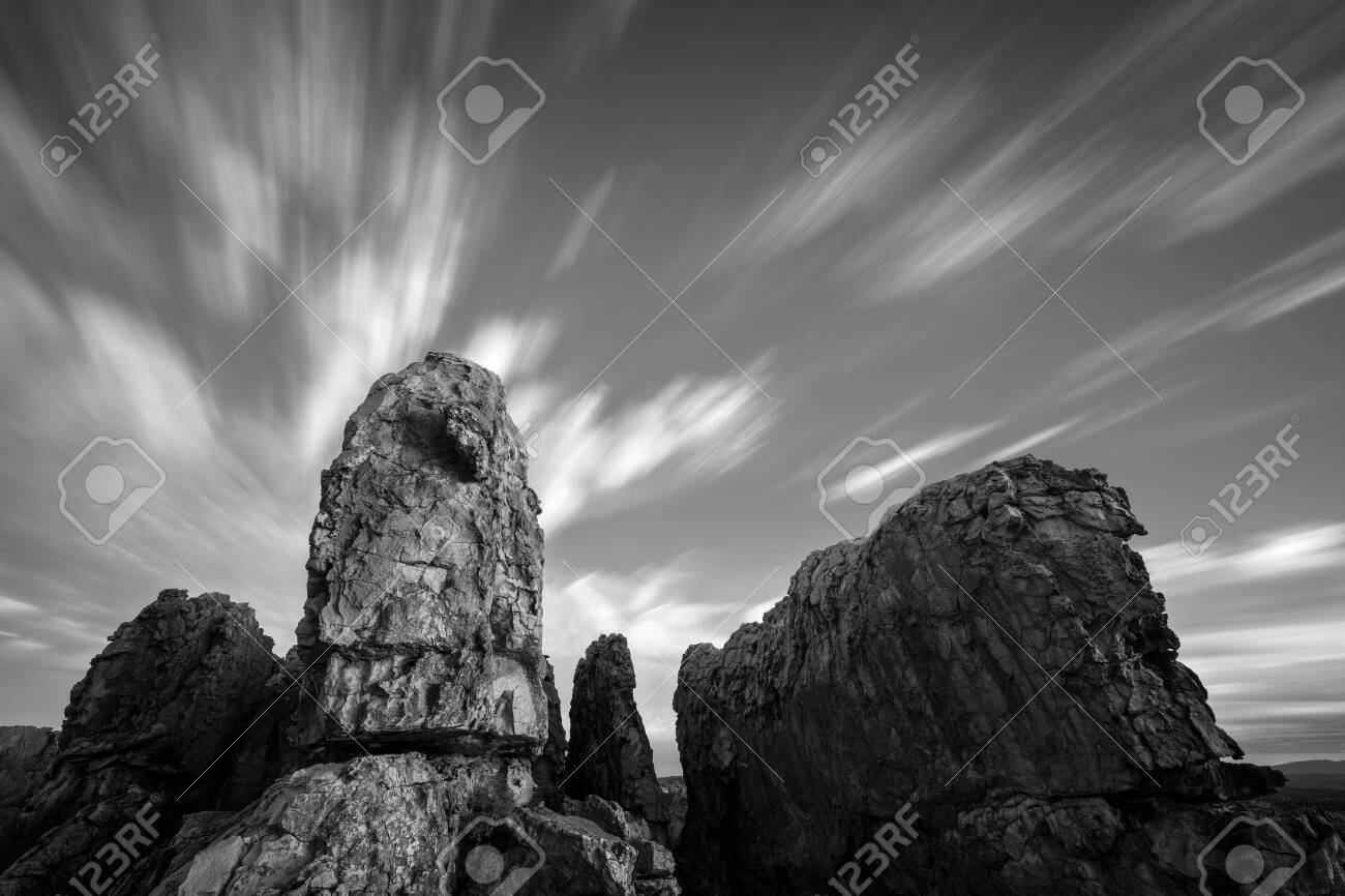 A stark black and white long exposure landscape with majestic rock formations in the foreground and fast moving clouds in the sky, taken in the Cederberg mountains in South Africa. - 142556013