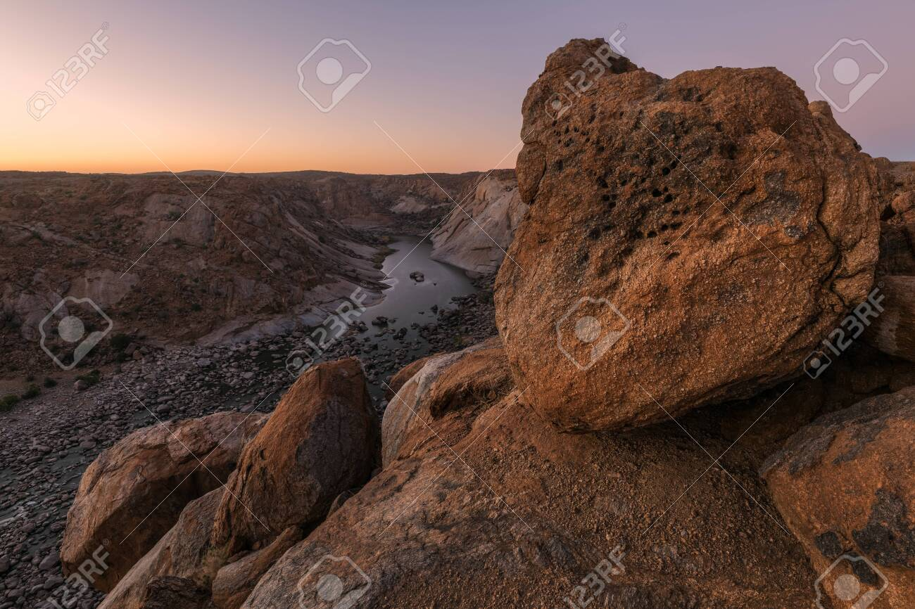 A beautiful landscape view of the Augrabies Falls Gorge, mountains and river in South Africa, taken before sunrise with large rocks in the foreground. - 142556569