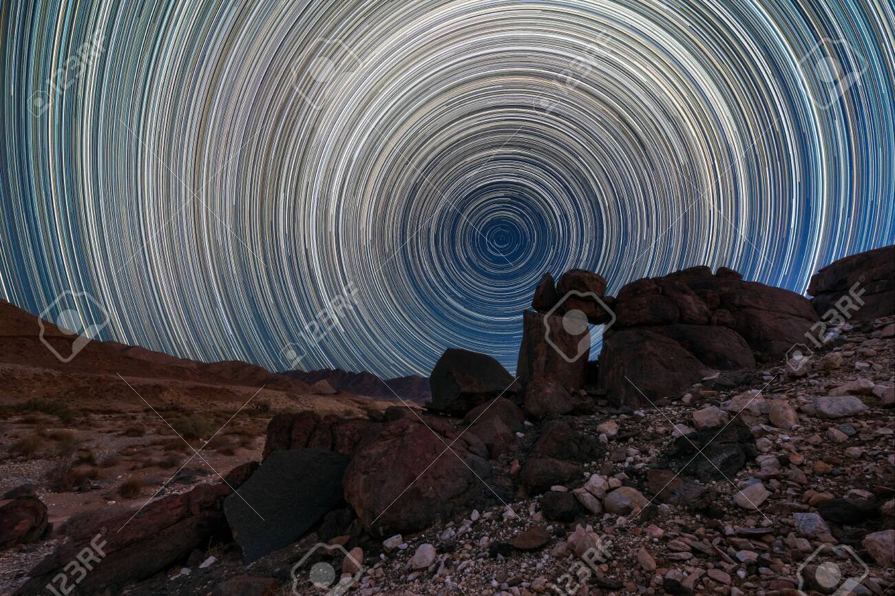 A beautiful night sky landscape with circular star trails, and interesting rock formations in the foreground and mountains on the horizon, in the Richtersveld National Park, South Africa. - 142556570