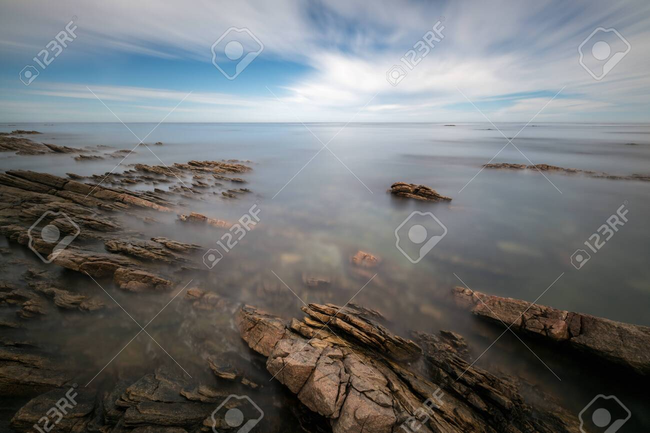 A tranquil long exposure seascape of moving clouds and waves, creating a beautiful moody mist around the dramatic rocks in the foreground, taken in Port Nolloth, South Africa. - 142556604