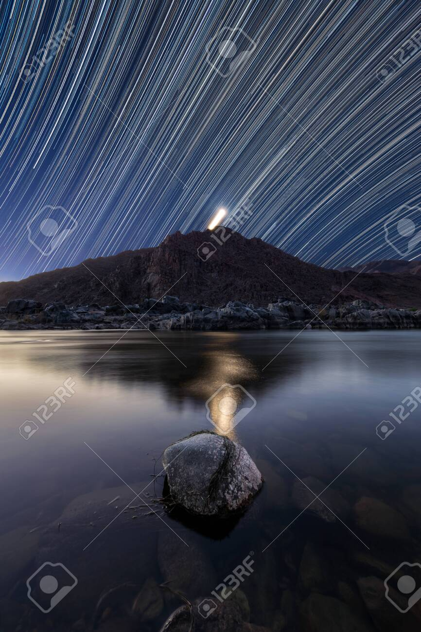 A beautiful vertical night sky landscape with star trails against a deep blue sky and the Moon setting behind mountains, reflecting in the Orange River, taken in the Richtersveld South Africa. - 142556638