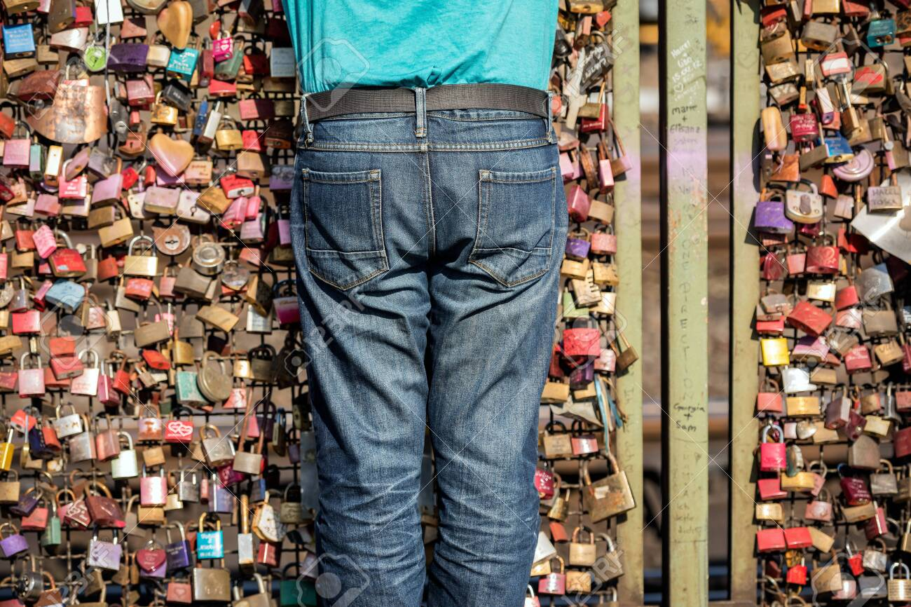 An abstract photograph of a torso of a person standing in front of the hundreds of love locks attached to the Hohenzollern Bridge in Cologne, Germany. - 142589313