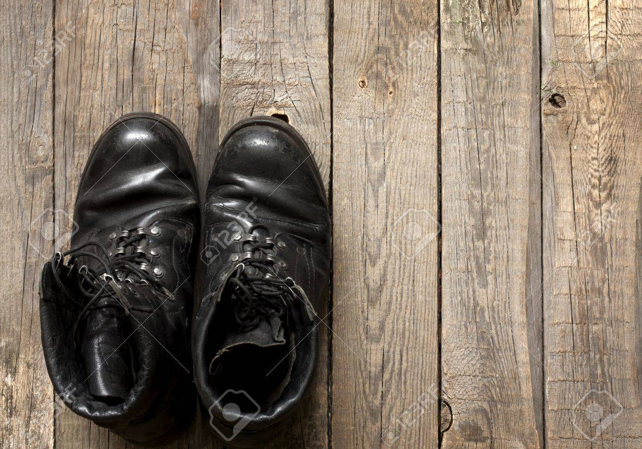 Old military shoes on wooden boards abstract background concept Stock Photo - 18436720