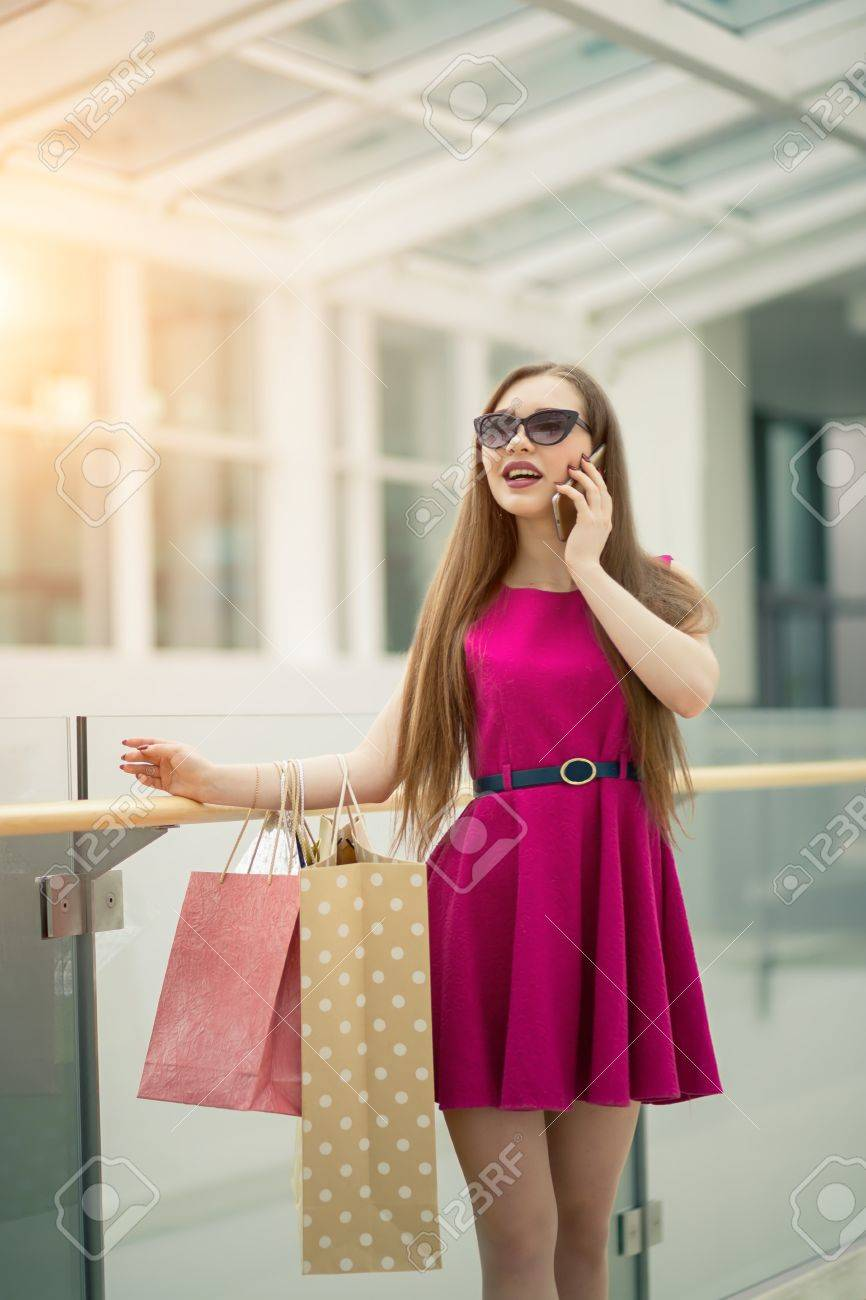 9e8193e4ca Beautiful young woman with shopping bags using her smart phone with smile  while standing at the clothing store