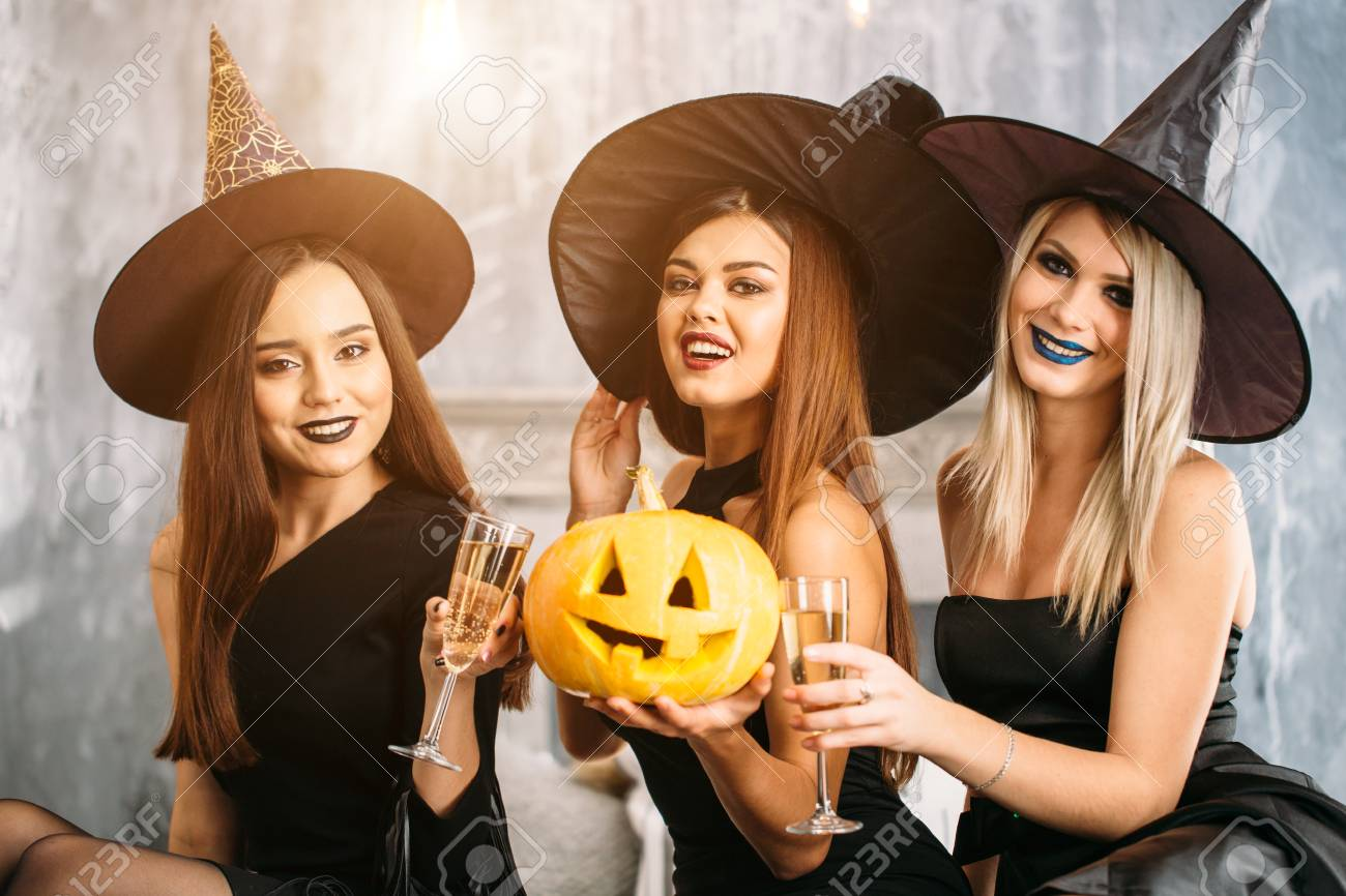 three friends sit on bed and drink champagne Halloween party - 88086340