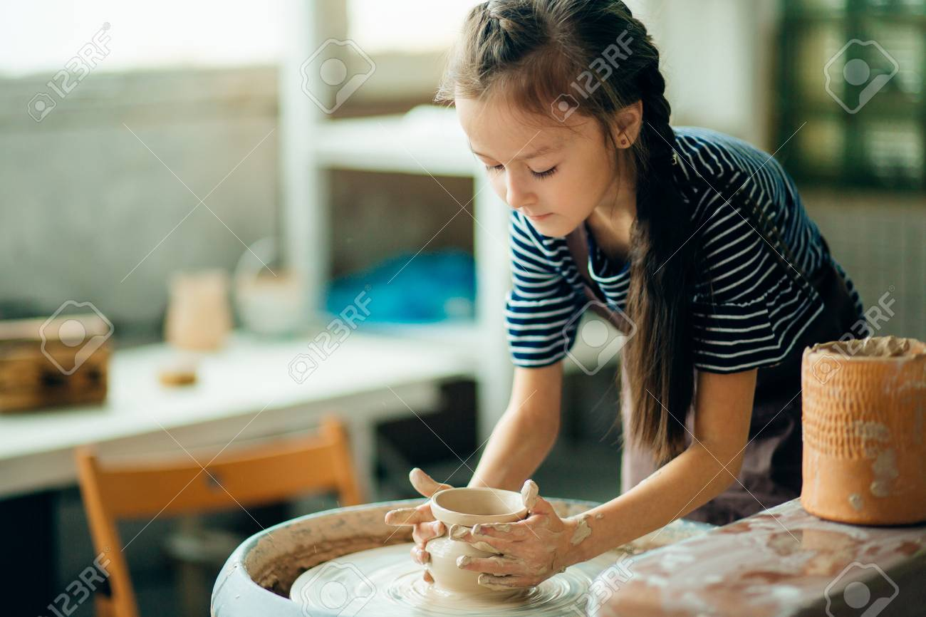 Child sculpts from clay pot. modeling on potter wheel. - 91678839