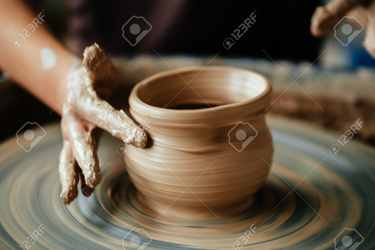 Female potter working at throwing wheel at studio. Clay workshop - 91695865