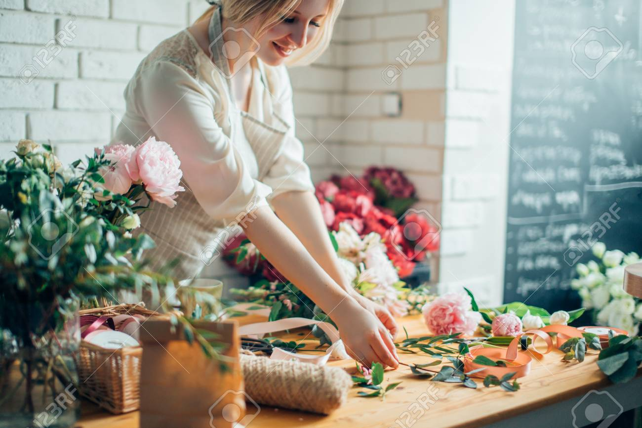 Florist workplace: woman arranging a bouquet with flowers - 91682177
