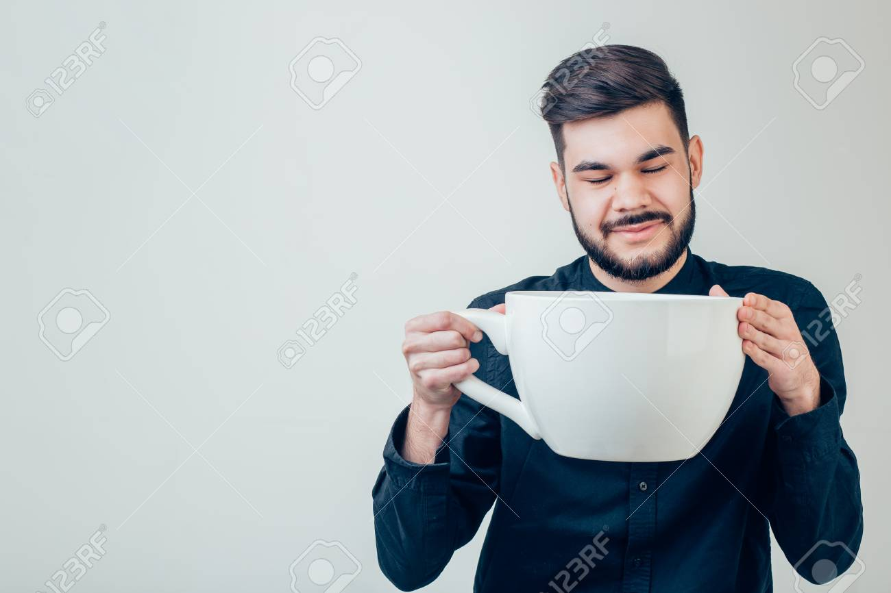 business man holding a funny huge and oversized cup of black coffee in caffeine - 91702028