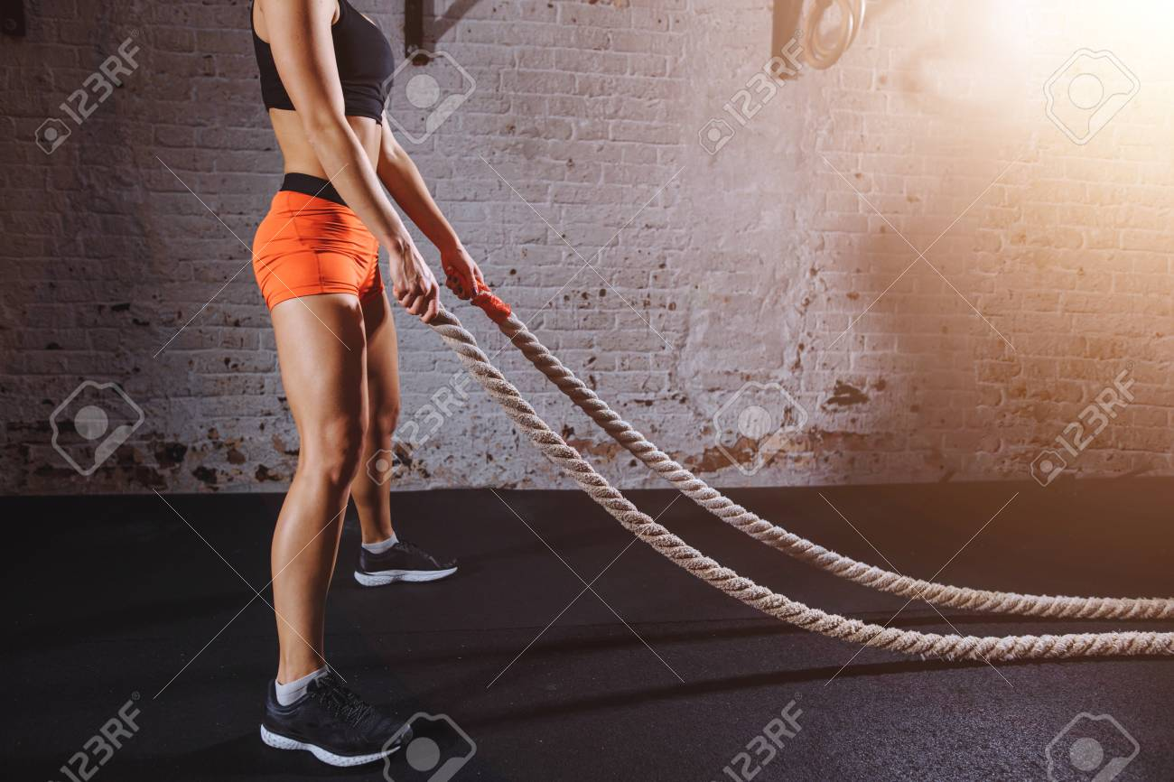 Young woman preparing to working out with battle ropes in cross fit gym - 91857440