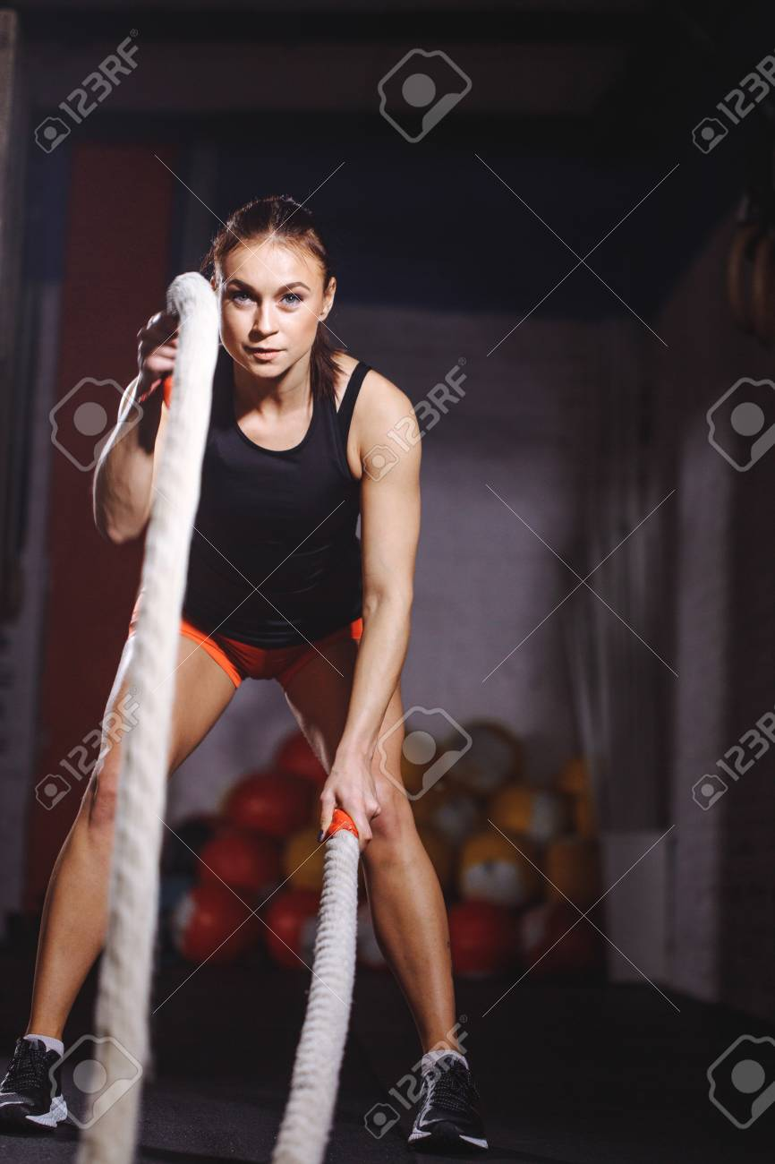Fit sportswoman working out in gym doing cross fit exercise with ropes - 93338035