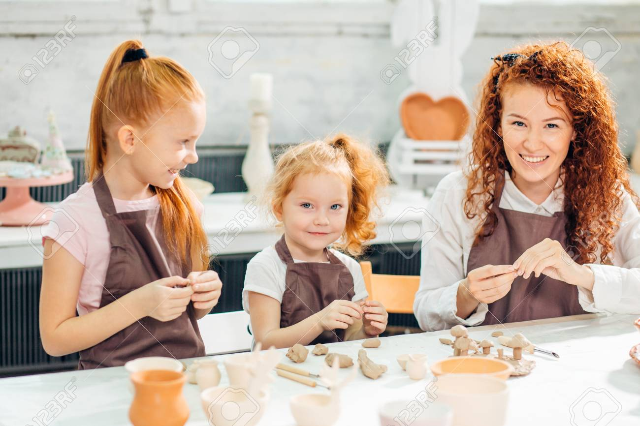 redhead mother and two daughter mold with clay, pottery children - 93387855