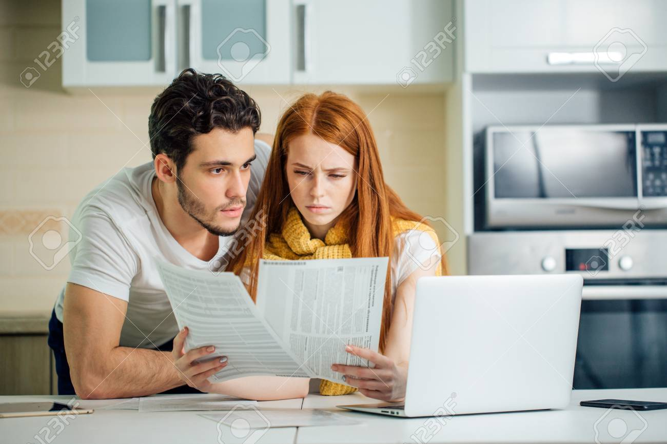 family managing budget, reviewing their bank accounts using laptop in kitchen - 93459151
