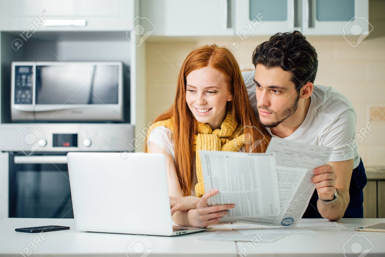 cheerful young couple calculating their bills at home - 93406915