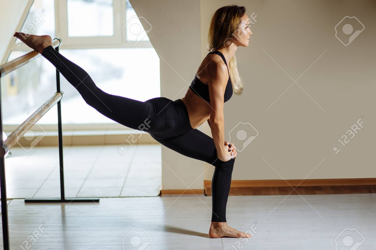 Girl smiling and looking in mirror while stretching body in fitness class - 94924305