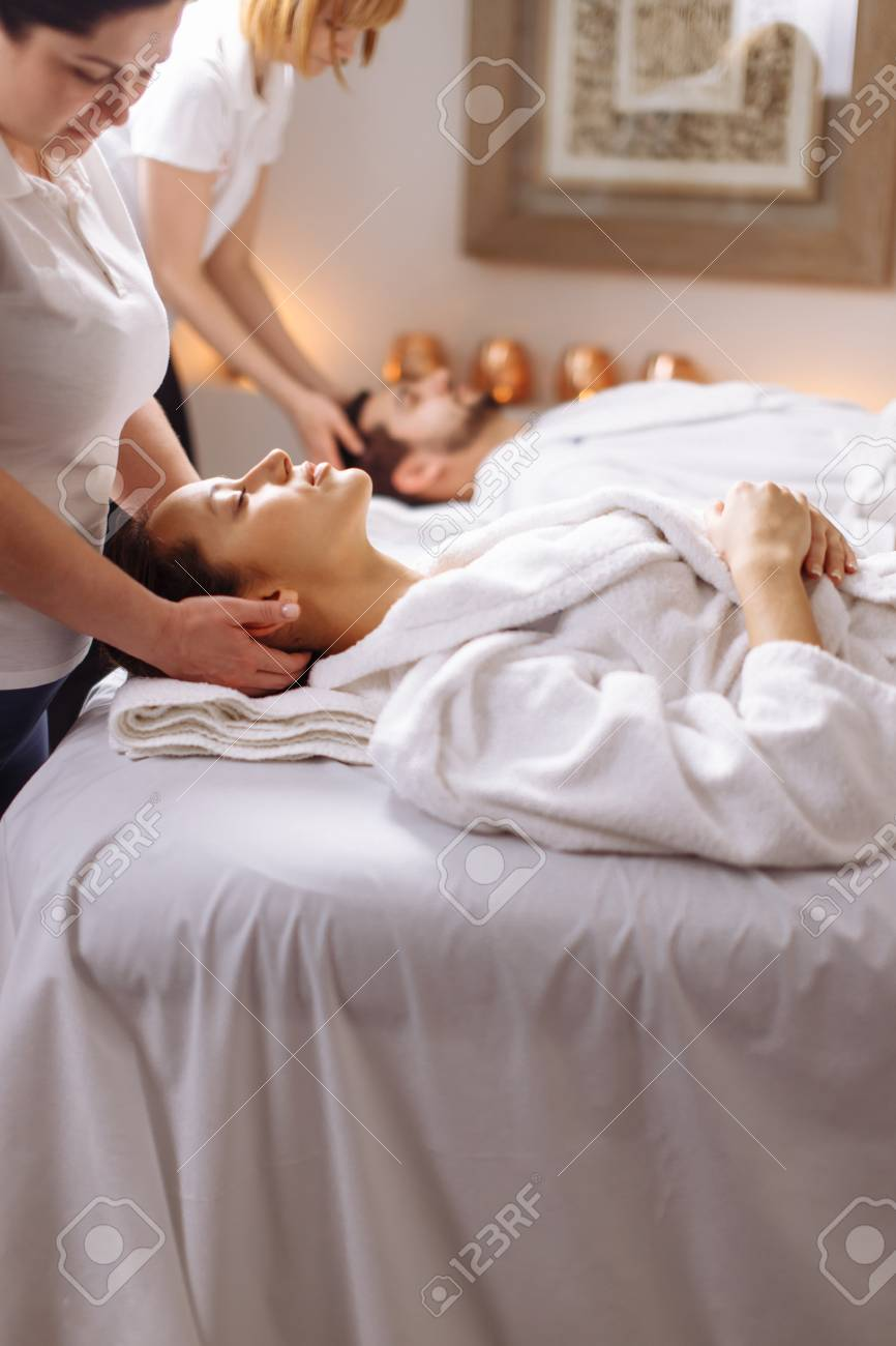 Young couple receiving head massage at beauty spa - 94924892