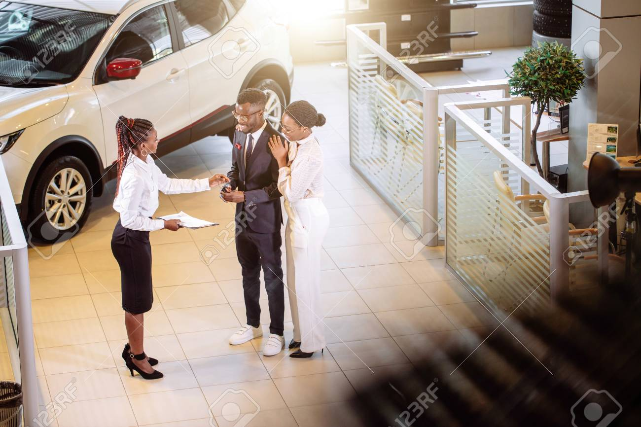 car salesman standing at dealership telling about features of car to customers - 94925656