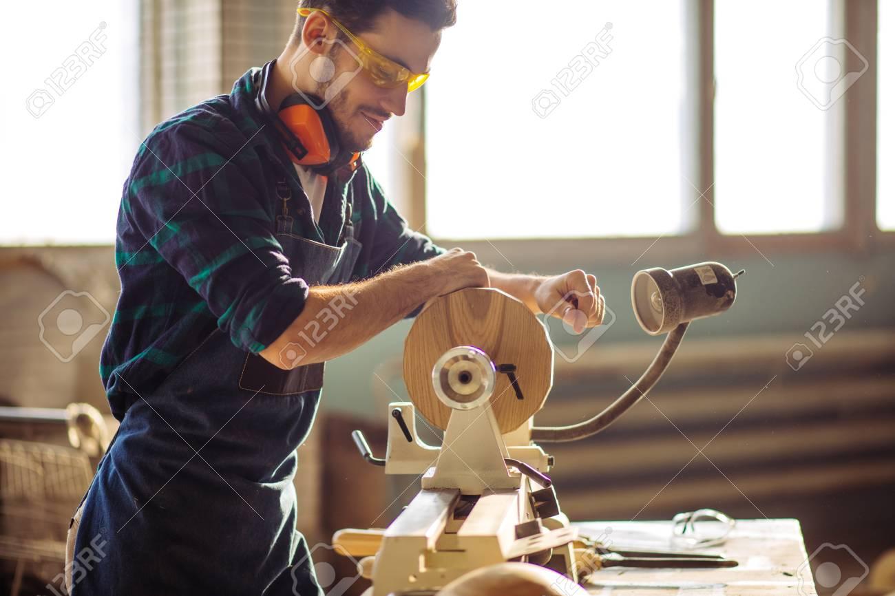 attractive man begin doing woodwork in carpentry - 96502095