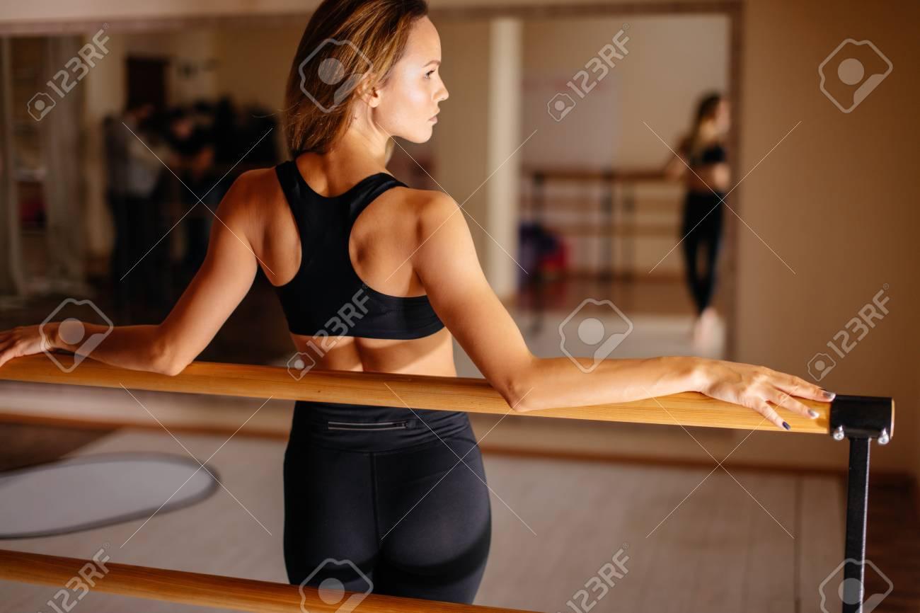 woman dancer posing near barre in ballet studio. - 96503407