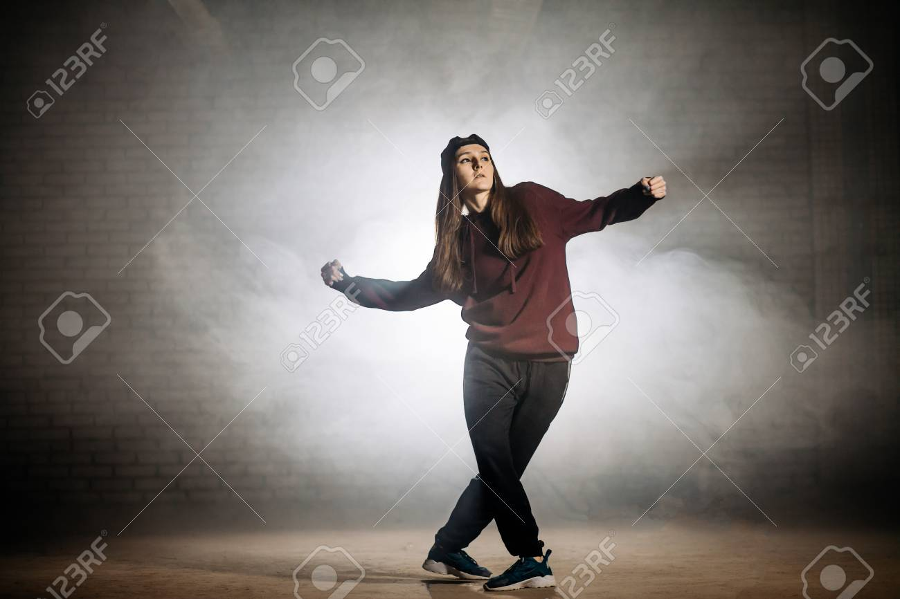 Young Female With Crossed Legs Dancing Crip Walk Outside Stock Photo