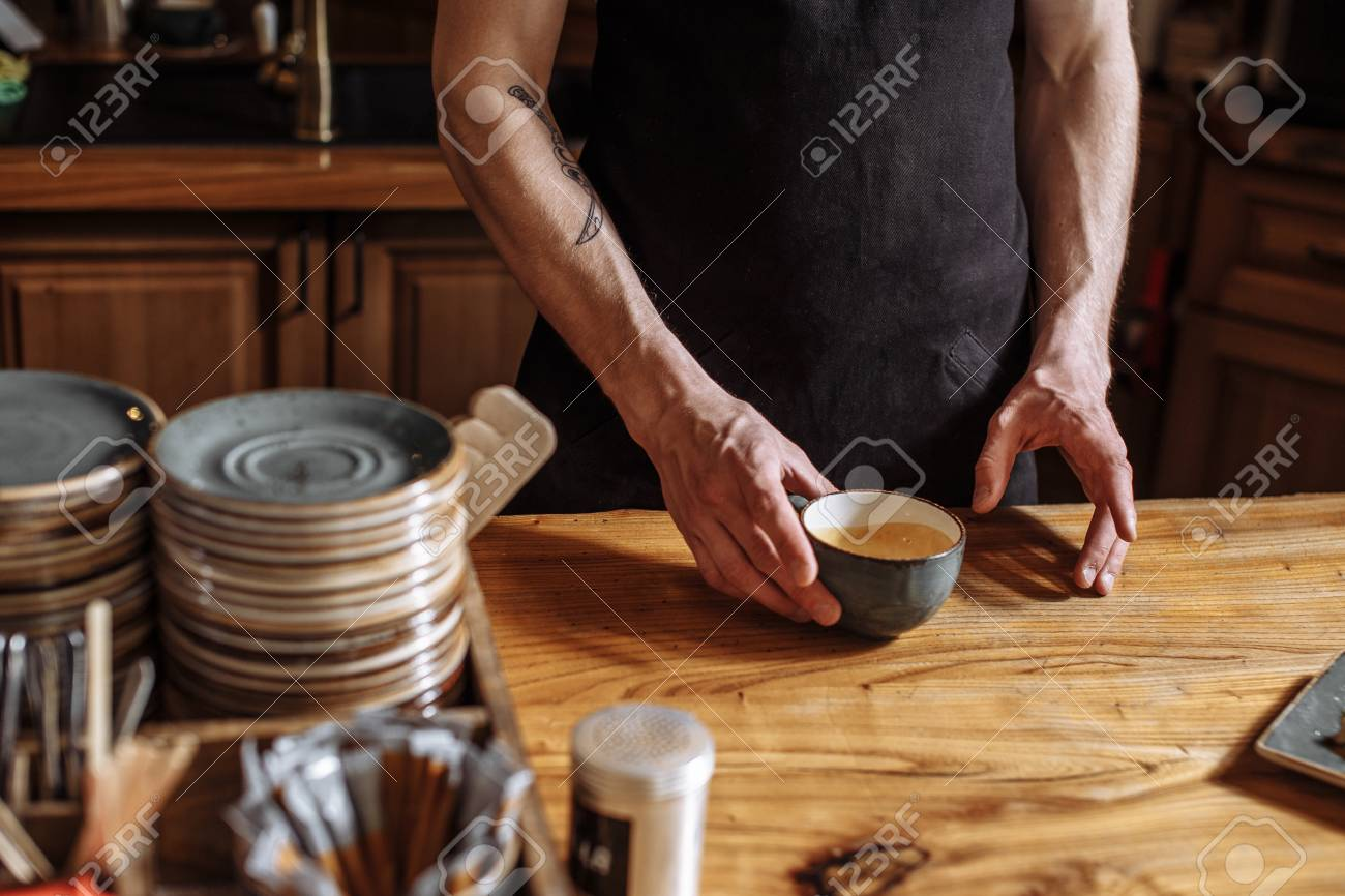 man is holding a cup with coffee-grounds - 106654814