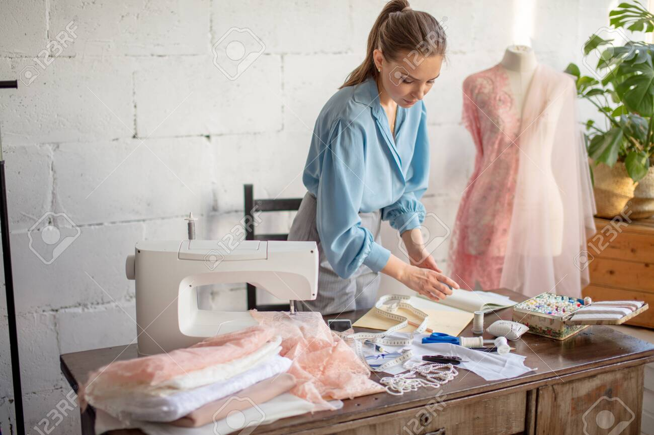 Pleasantly looking wearing ponytail is sitting at her worktable with laid tailoring equipment, containers full of thread spools, thinking of color while choosing thread for sewing. - 118795883