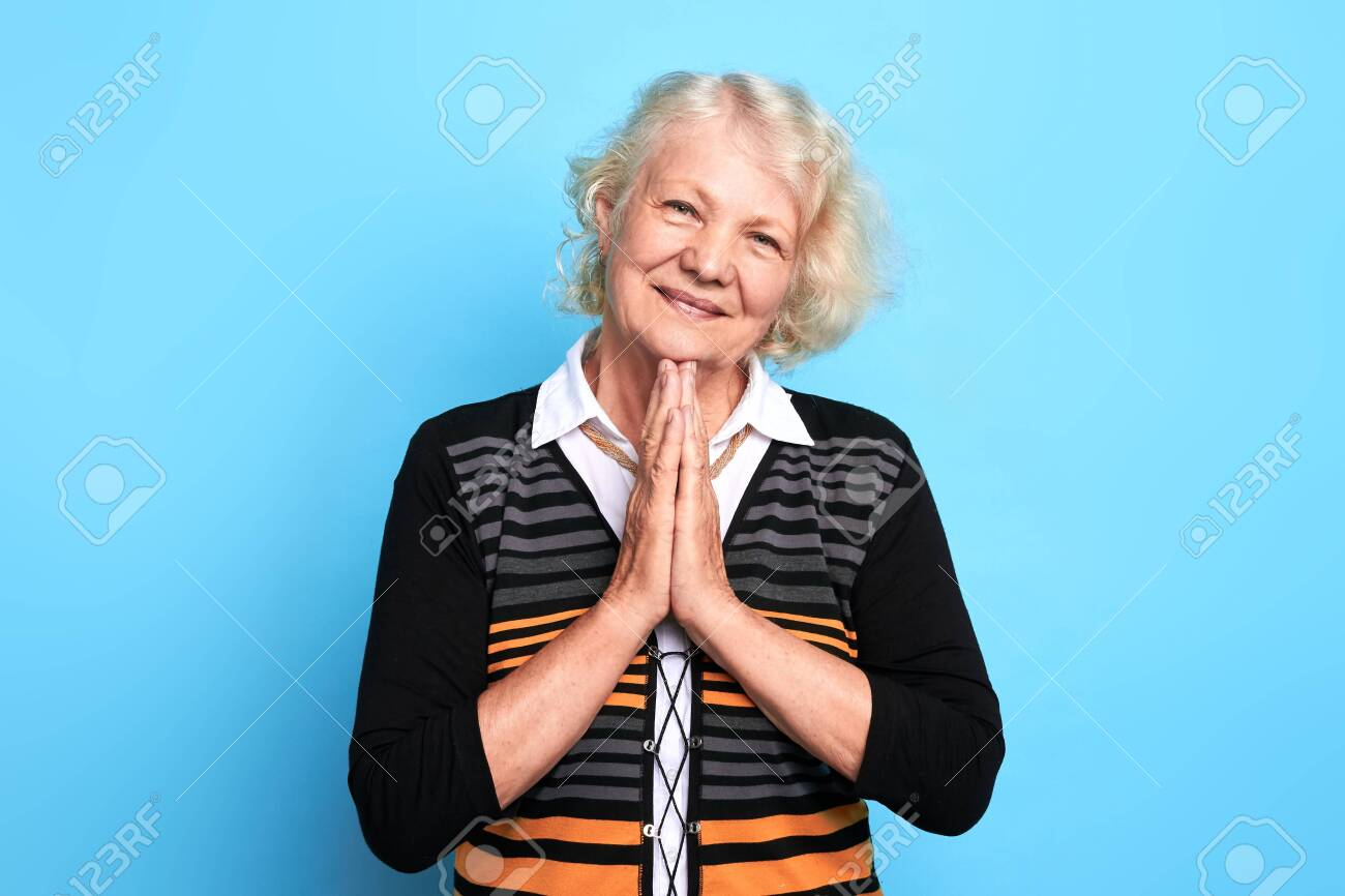 Senior happy blonde woman keeping palms together, praying the God. close up portrait. isolated blue background. strength of pray, kindness, body language, wish. - 127369640