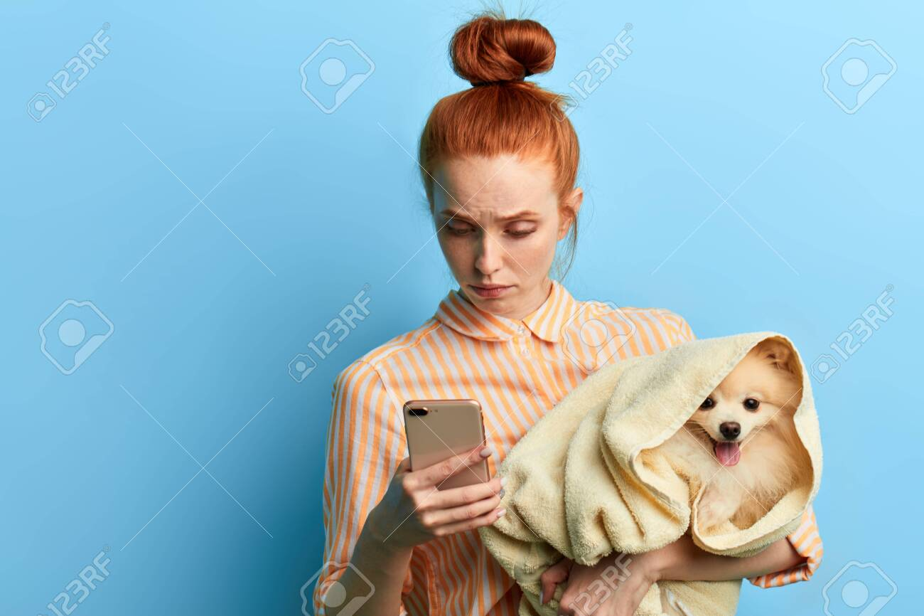 unhappy sad red-haired woman holding a towel with a dog and making a phone call, girl waiting for a vet, as her dog is ill. isolated blue background, studio shot.depression - 128548605