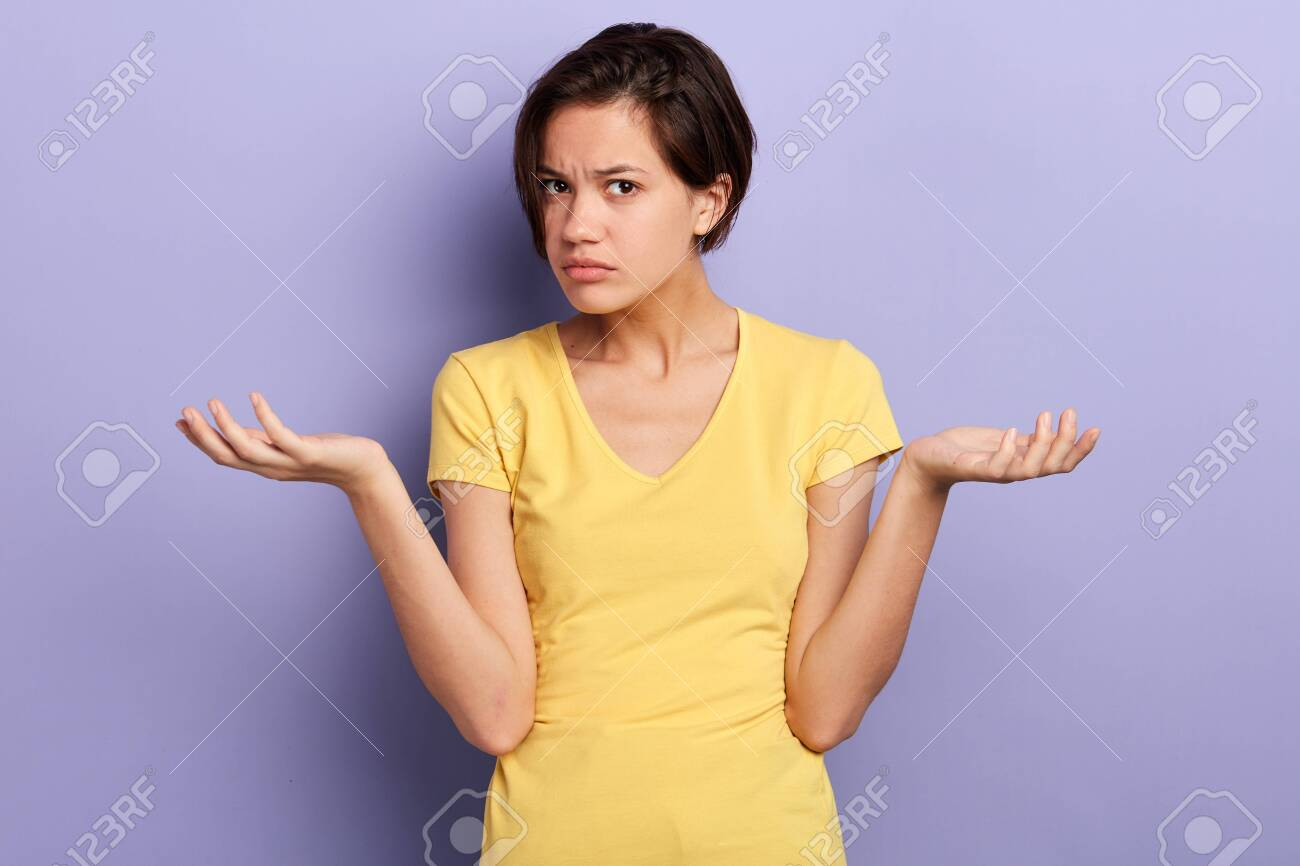 serious girl cannot understand her friend, woman being puzzled with suggestion, offer, close up portrait, isolated violet background, studio shot - 129720439