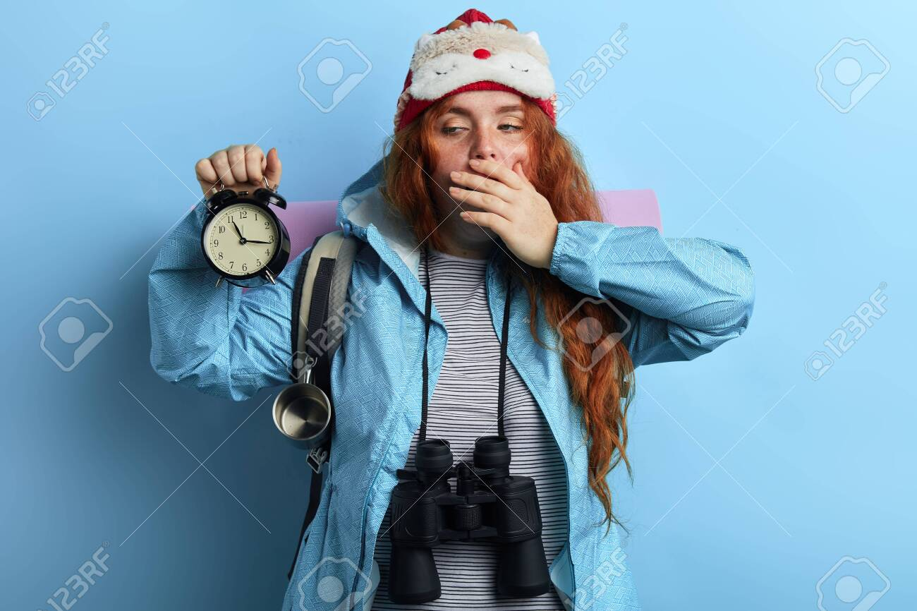 sleepy young hiker holding a clock, has problems to get up i the morning, tourist has slept badly. insomnia concept - 129589814