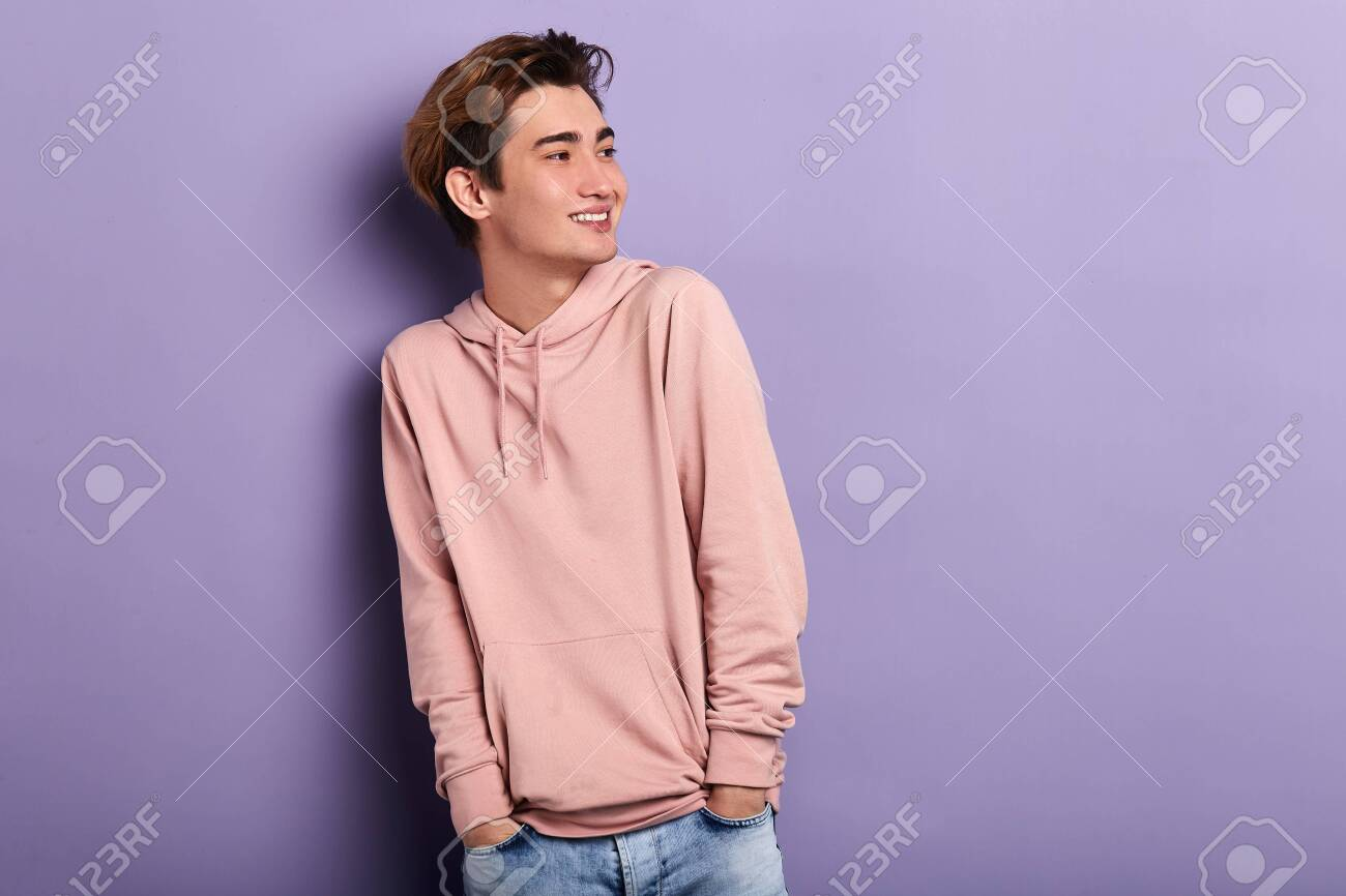 smiling cheerful man wearing pink hoodie, jeans looking aside, waiting for his friends. copy space. fashion, people, youth - 129704802