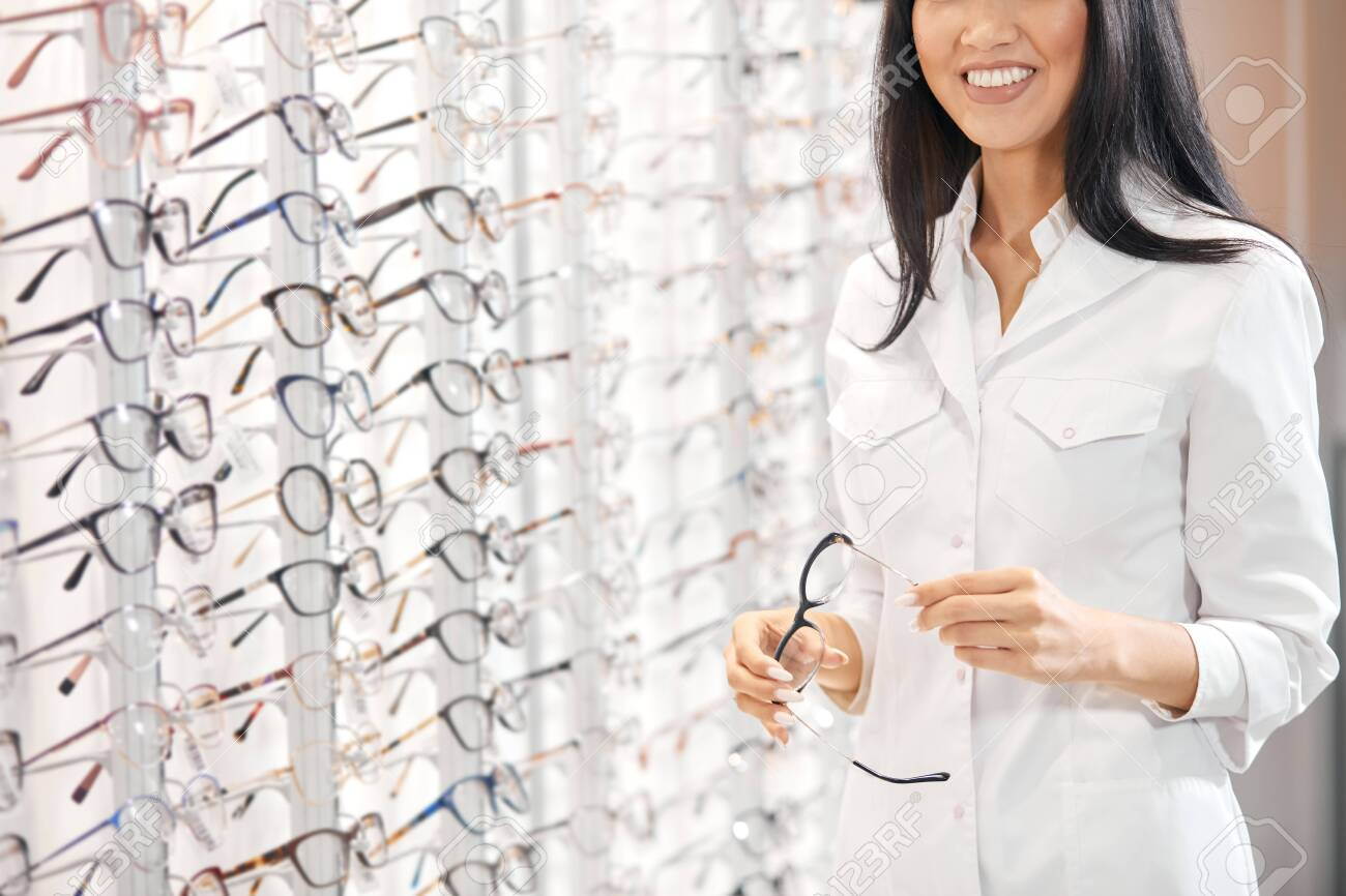 Asian woman in white medical uniform holding glasses, recommending customers to buy them. close up cropped photo - 130936518