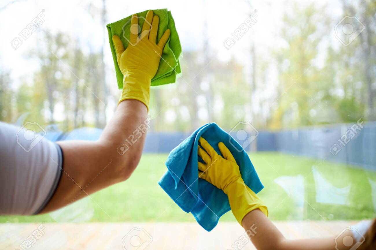 Closeup of cleaners holding rags, wearing yellow rubber gloves. Cleaning glass of window - 132640190