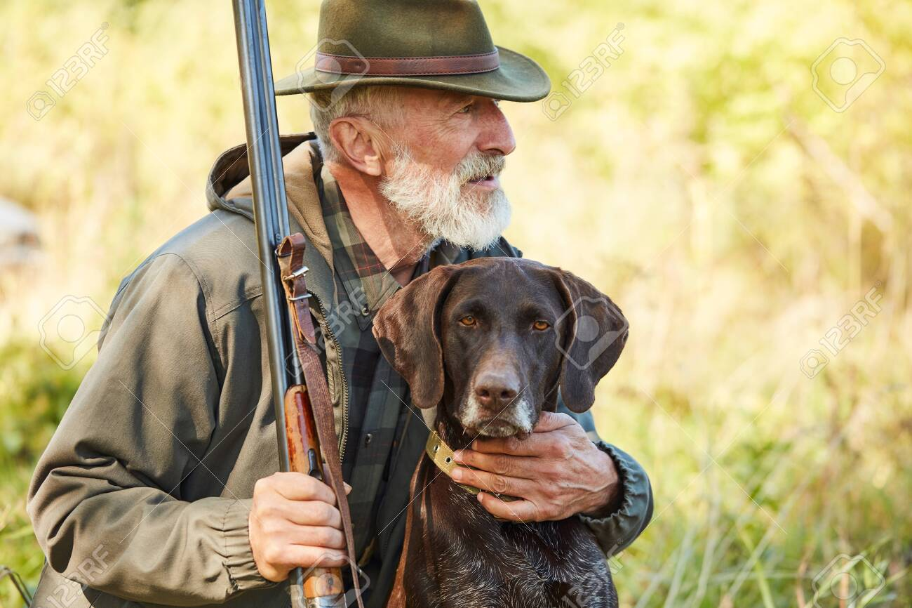 Caucasian mature man with gun and dog sit searching prey. Bearded man in hunting clothes. Autumn - 133175309