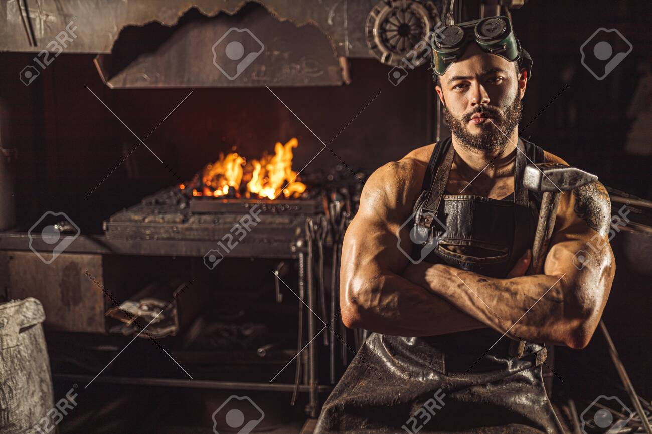 Portrait of serious confident strong young metalworker in black apron stand looking at camera, work in workshop - 135675953