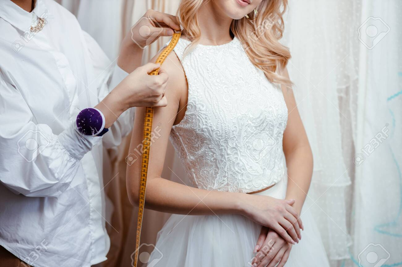 wedding concept. young tailor woman take measures of future bride, going to buy designers wedding dress. Sewing in salon - 137460508