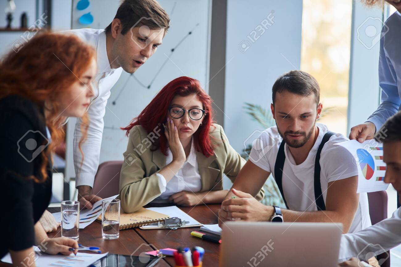 Young group of businesspersons involved in creative business discussing work in the office and sit in shock while looking at screen of laptop, office background - 137526488