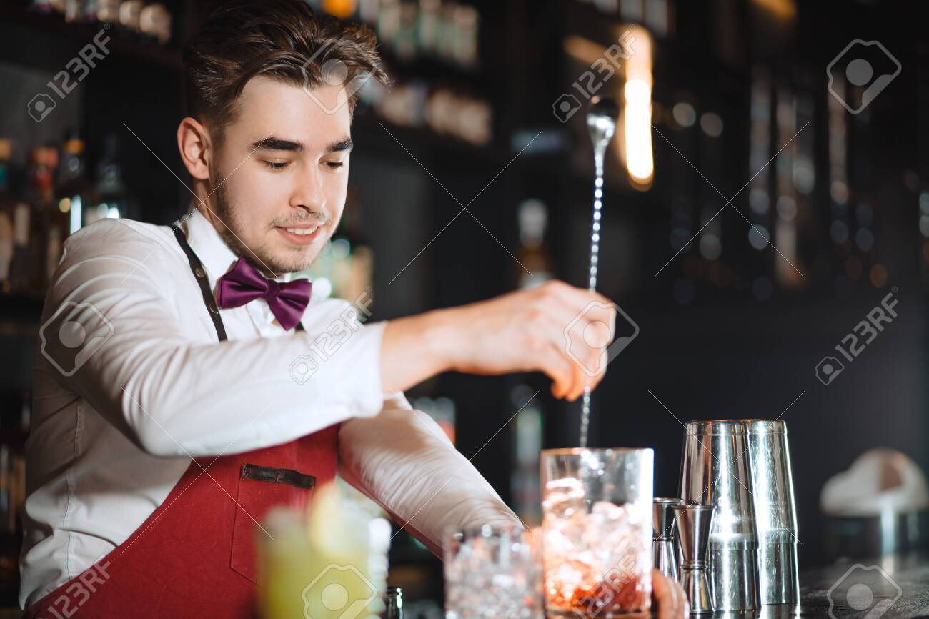 Barman holding a long spoon and glass filled with ice cubes and red drink mixing the beverage on the bar counter of night club - 151422027