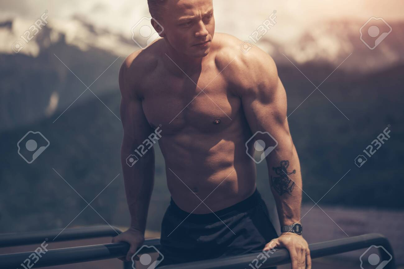 Motivated athletic shirtless man does bodyweight push ups on low horizontal bars at cool mountains area outdoor gym in the early morning. - 151945292