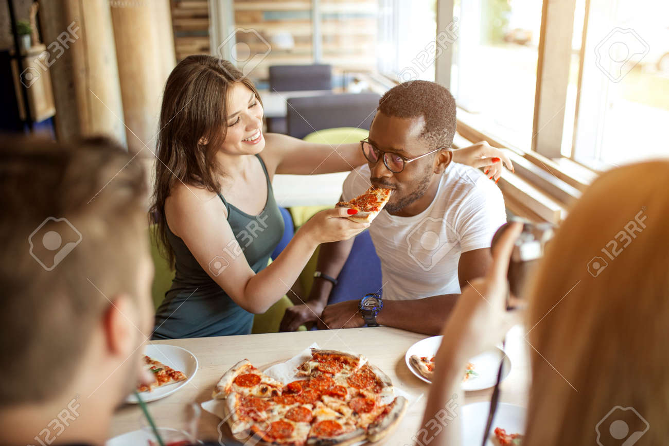 Young multiracial diverse colleagues eating pizza during their lunch time at office pizzeria, playing team building game, feeding his partner with tasty pizza - 151952561