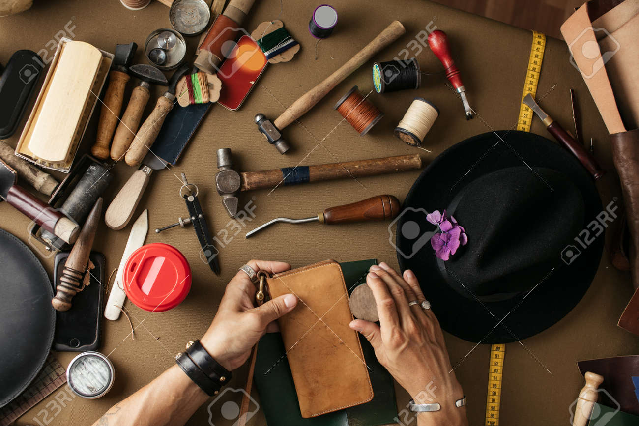 Close-up of male master cutting piece of leather with crafting tools for future wallet at workshop. High angle view of cobbler working place. - 152781273