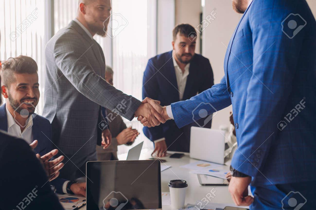 Business people in formal wear shaking hands, finishing up a meeting, establishing multi-ethnic partnership, making deal. - 153174042