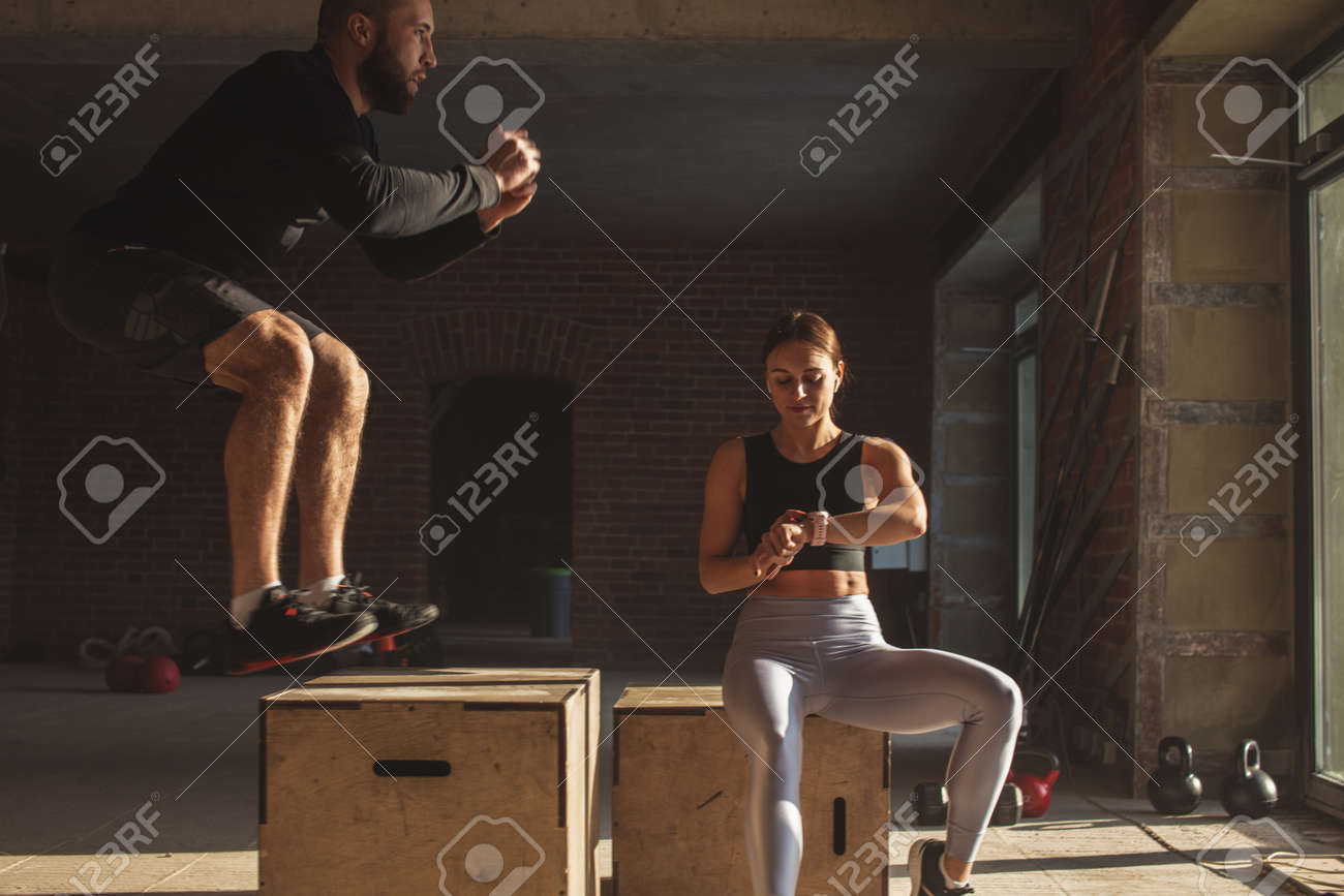 Female personal instructor checking the time while her athletic male trainee doing jump squats at crossfit workout - 153641182