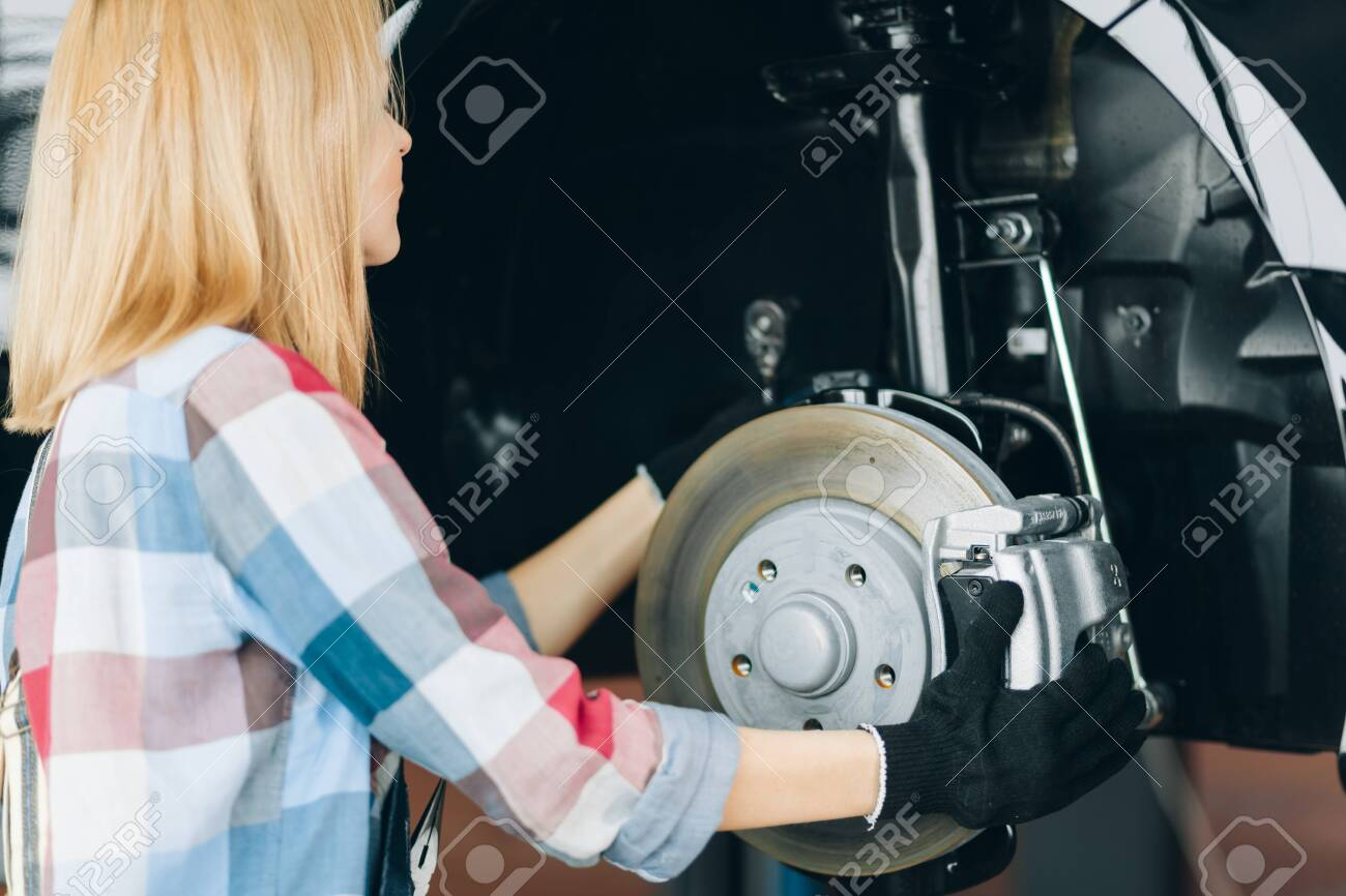 girl in gloves and checked shirt holding brake disks at workplace. close up back view photo. pastime - 153939786